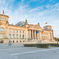 German Reichstag, the German parliament building in Berlin at sunset. Some german flags and one European waving. Politics and architecture concepts.